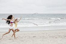 Weibliche Teenager, die Jagd auf Vögel am Strand