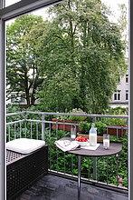 Milch, Erdbeeren, Brillen und Zeitung auf Balkon Tisch