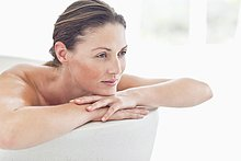 Serene woman leaning on edge of bathtub