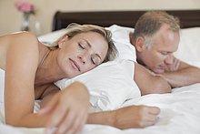 Entspanntes Paar schläft im Bett
