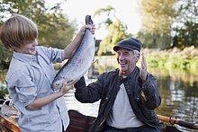 Enkelsohn angelt einen Fisch mit Großvater im Hintergrund