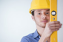 Young man wearing hard hat using mechanic's level
