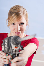 Young woman holding drilling machine