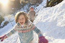 Junge und Mädchen rennen im Schnee