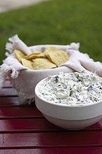 Artischockendip und Chips auf Gartentisch