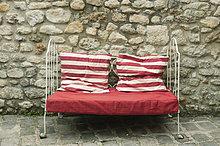 Loveseat mit roten Kissen vor der Steinwand