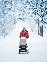 Lächelnde Mutter Wandern mit Kinderwagen in Winterlandschaft