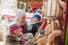 Österreich, Salzburg, Mutter mit Kindern auf dem Weihnachtsmarkt, lächelnd