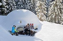 Österreich, Salzburger Land, Vater und Sohn beim Iglu sitzend