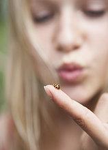 Österreich, Teenagermädchen schaut auf Marienkäfer am Finger