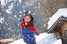 Lächelnde Frau wirft einen Schneeball