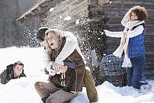 Lachende Freunde genießen Schneeballschlacht