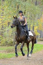 Junge Frau reitet auf einem Pferd