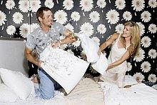 Paar mit einen Kissen kämpfen im Bett
