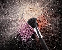 Makeup-Pinsel über mehrfarbigen Rouge-Spritzern