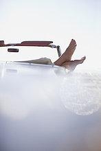 Frauenfüße auf dem Cabriolet liegend