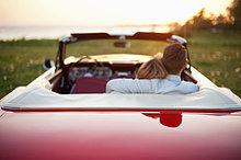 Rückansicht des jungen Paares mit den Armen im Cabrio auf dem Feld sitzend