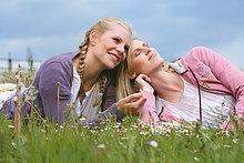 Zwei fröhliche junge Frauen liegen auf einer Wiese