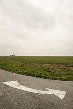 Weißer Wegweiserpfeil am Leuchtturm Westerhever