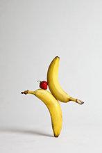 Eine Erdbeere, die zwischen zwei Bananen balanciert.