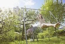 Young woman swinging while man raking lawn in background
