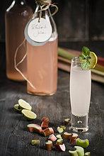 Glas Rhabarber mit Rhabarbersaftflasche und Rhabarberstücken auf Holztisch, Nahaufnahme