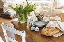 Weisser Tulpenstrauss in Glasvase neben Tellerstapel, Weingläsern, Dekofeigen und Deko-Artischocke