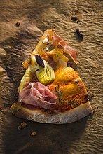 Ein Stück Pizza mit Pancetta, Artischocken und schwarzen Oliven