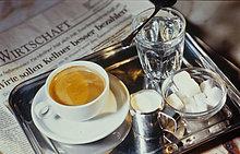 Kaffee mit Milch, Wasser und eine Zeitung
