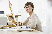 Porträt einer lächelnden Frau an der Staffelei auf dem Tisch