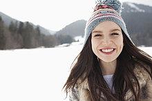 Nahaufnahme Porträt einer glücklichen Frau mit Strickmütze im Schneefeld