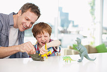 Father and son playing with plastic dinosaurs
