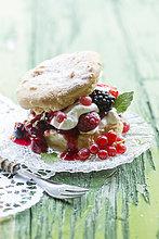 Puffs mit Sahne und Beeren auf grünem Tisch, Nahaufnahme