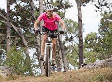 Frau fährt Mountainbike im Wald