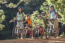Porträt einer lächelnden Familie auf Mountainbikes im Wald