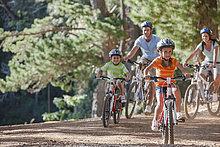 Glückliche Familie beim Mountainbiken im Wald