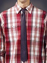 Mann in einem roten Tartan-Hemd mit einer gestreiften Krawatte