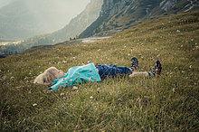 Italien, Provinz Belluno, ßeneto, Auronzo di Cadore, kleiner Junge liegt auf einer Alm bei Tre Cime di Laßaredo.
