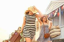 Teenagermädchen gehen an Strandhütten vorbei