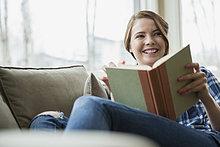 Frau liest Buch auf Sofa im Wohnzimmer