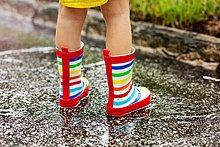Beine des Mädchens in Gummistiefeln in Regenpfütze stehend