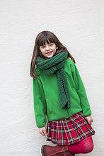 Porträt des lächelnden Mädchens mit grünem Schal, grüner Jacke und Kilt