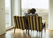 Seniorenpaar sitzt Seite an Seite in Sesseln und schaut durchs Fenster.