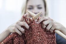 Nahaufnahme einer Frau, die eine Decke strickt