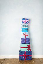 Stapel von sechs verpackten Weihnachtsgeschenken auf Holzboden