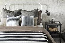 Gestreifte und gemusterte Kissen und Decken auf dem Bett
