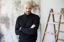 Porträt eines Mannes mit gekreuzten Armen in schwarzem Rollkragenpullover