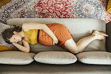 Eine schwangere Frau macht zu Hause ein Nickerchen auf ihrer Couch.