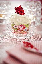 Schweden, Uppland, Nahaufnahme von Cupcake mit Glasur und Preiselbeeren