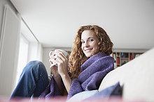 Lächelnde Frau zu Hause auf der Couch sitzend, Tasse haltend
